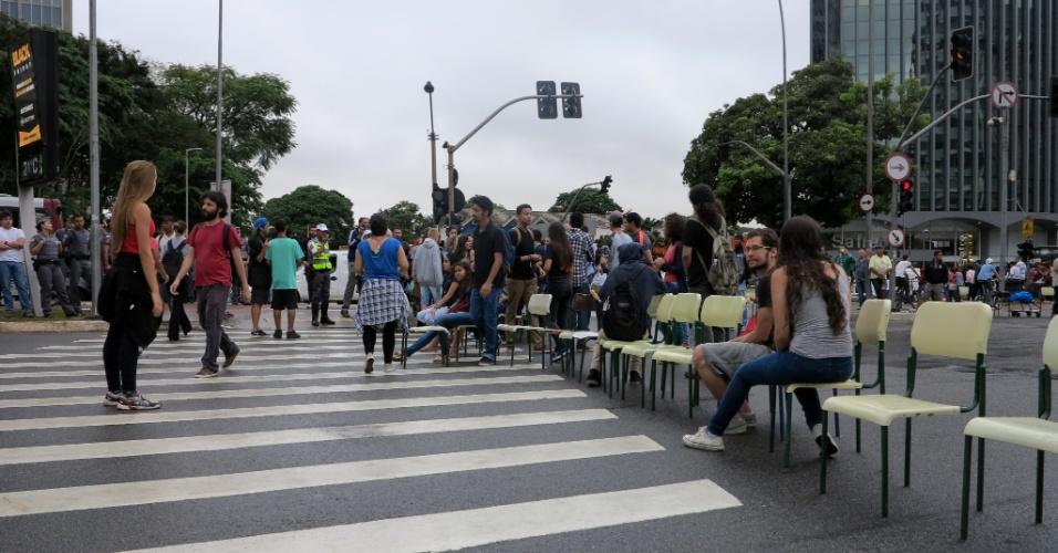 30.nov.2015 - Estudantes protestam na manhã desta segunda-feira (30) no cruzamento das avenidas Brigadeiro Faria Lima e Rebouças, na região de Pinheiros, na zona oeste de São Paulo. Eles colocaram cadeiras para bloquear as duas vias. Pessoas que passavam pelo local se juntaram à manifestação. Os alunos protestam contra a reestruturação das escolas públicas estaduais, proposta pelo governo estadual. Policiais militares acompanham o ato. O bloqueio do cruzamento interrompe o trânsito no local e provoca lentidão na região