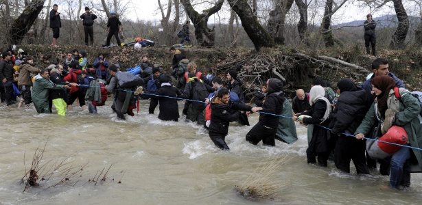 Refugiados tentam cruzar rio próximo à fronteira entre a Grécia e a Macedônia