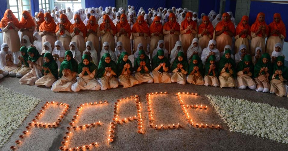 """9.ago.2016 - Alunos de uma escola da cidade de Ahmedabad, na Índia, usam as cores do país enquanto oram pela paz mundial. O ato, que contou com a inscrição """"paz"""" feita com velas no chão, ocorre no dia do aniversário de 71 anos da explosão nuclear em Nagasaki, no Japão"""