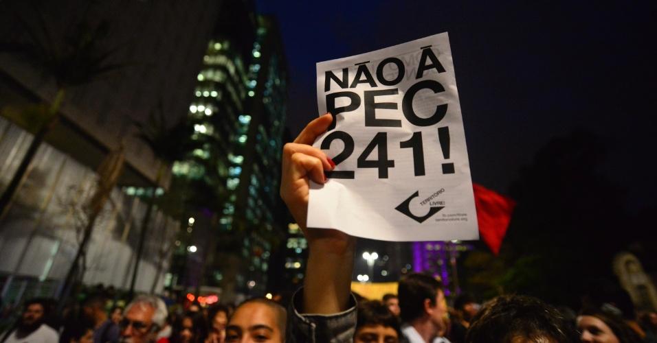 25.out.2016 - Manifestante ergue cartaz contra a PEC 241 durante protesto na avenida Paulista, em São Paulo
