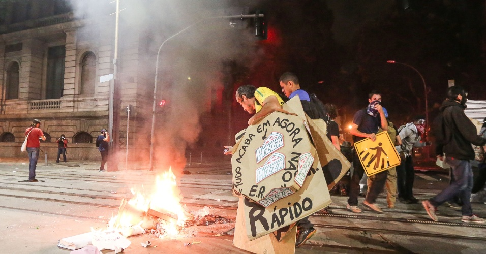 Manifestantes observam fogo causado após conflito com a PM no Rio de Janeiro