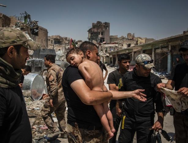 Suspeito de ser militante do Estado Islâmico carrega menino que usava apenas um colete ensaguentado e um short sujo em Mossul