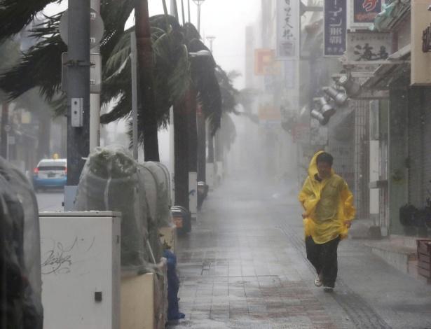 Homem caminha em rua da cidade de Naha em meio a forte chuva causada pelo Trami - Kyodo/via Reuters