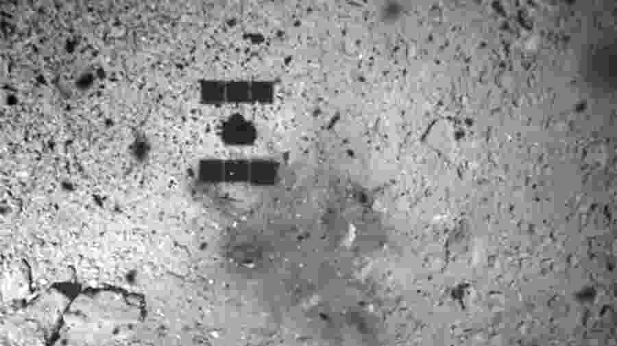 Foto tirada pela câmera ONC-W1 do asteroide Ryugu e recebida da sonda Hayabusa2 mostra a sombra da espaçonave japonesa Hayabusa2 (no topo à esquerda) sobre o asteroide Ryugu antes de aterrissar - AFP