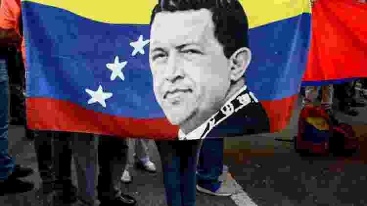 12.nov.19 - Manifestante segura bandeira com a imagem do presidente venezuelano Hugo Chávez (1954-2013) em protesto a favor do ex-presidente boliviano Evo Morales, em Caracas - Federico Parra/AFP