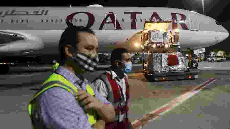 Funcionários do aeroporto internacional de Doha, no Qatar, usam máscara contra coronavírus - Karim Jaafar/AFP