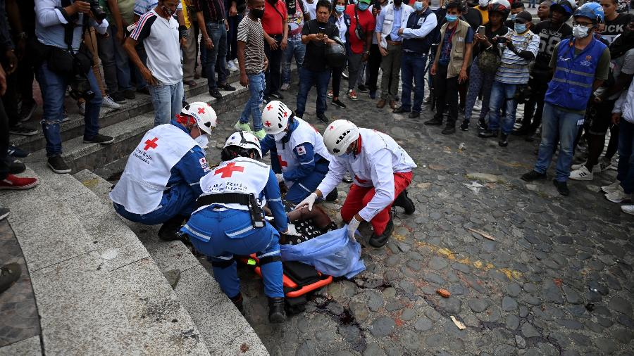 Equipes de resgate colocam um cadáver em uma maca durante protesto contra o governo do presidente colombiano Ivan Duque, em Cali, em 28 de maio  - LUIS ROBAYO/AFP