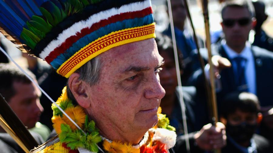 12.ago.2021 - O presidente Jair Bolsonaro com cocar indígena tira fotos na Praça dos Três Poderes, em Brasília - MATEUS BONOMI/AGIF/Estadão Conteúdo