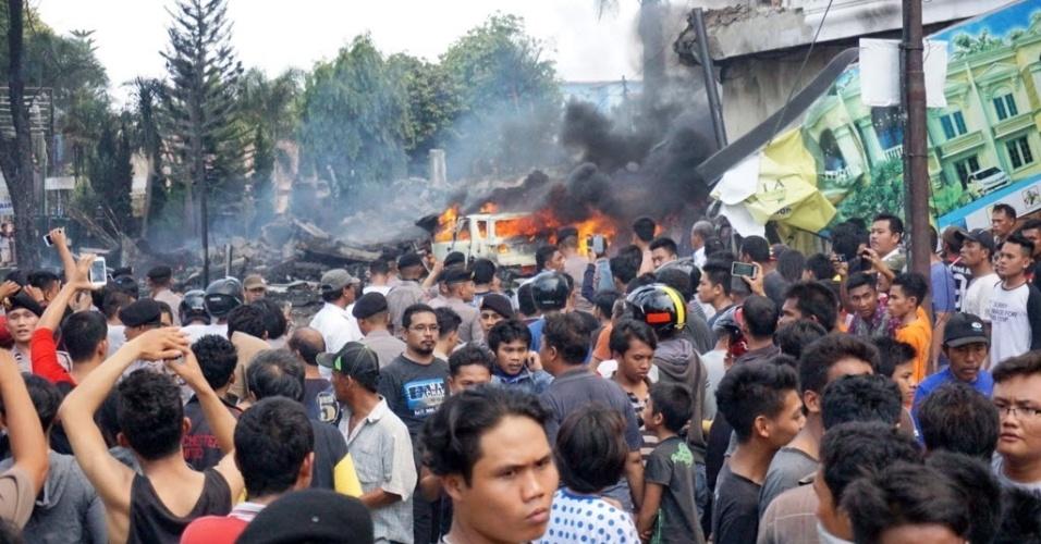 30.jun.2015 - Moradores se reúnem no local do acidente com um avião de transporte militar indonésio C-130 Hercules, em área residencial da cidade de Medan, na ilha de Sumatra, Indonésia. O acidente incendiou casas e veículos e matou mais de cem pessoas