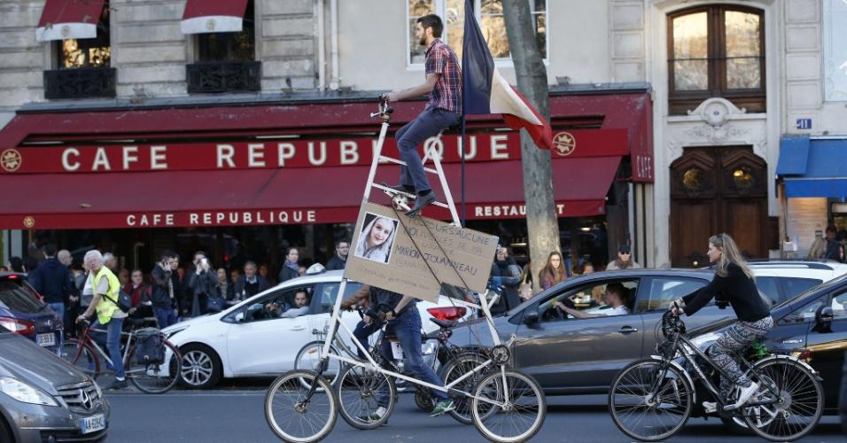 15.nov.2015 - Homem circula com cartaz em bicicleta pela Place de la Republique, em Paris, neste domingo. Ele diz que procura sua prima, de quem não tem notícias desde o ataque terrorista ao Bataclan na sexta-feira (13)