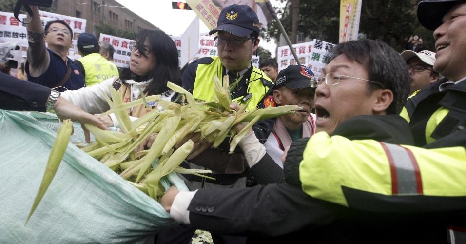 4.jan.2016 - Manifestantes tentam lançar espigas de milho e são impedidos por policiais durante protesto contra o acordo comercial com a China em frente ao Conselho de Agricultura, em Taipei, Taiwan