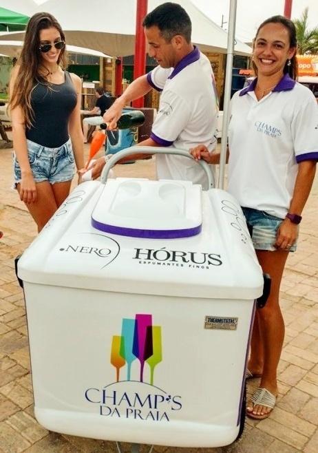 Proprietários da empresa Champ's da Praia, o casal Gazi Nóbrega e Larissa Calheiros serve espumante a cliente na praia da Atlântida (RS)