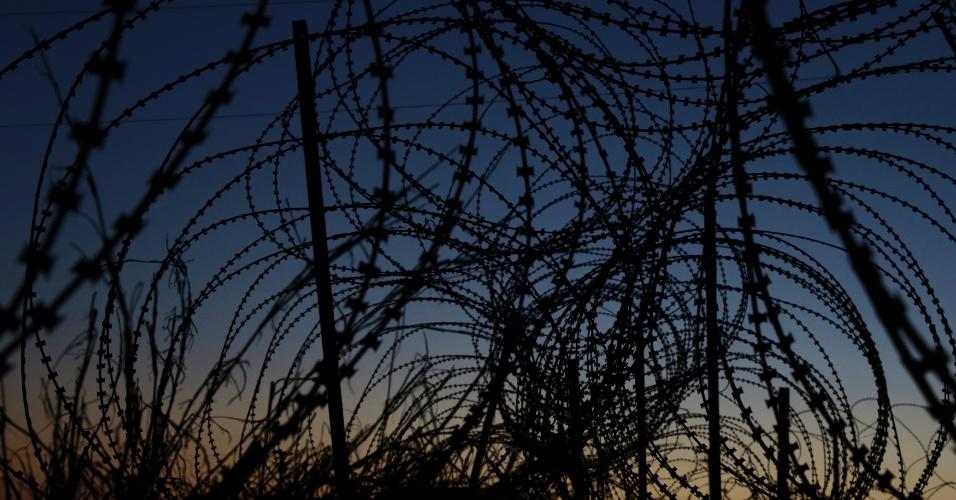 28.mar.2016 - Muitos dos detentos de Guantánamo nunca foram julgados. O governo norte-americano alega que alguns são muito perigosos para serem transferidos, mas jamais poderão ser julgados por cortes nos EUA, já que a Justiça americana não aceitaria as provas ou a forma como foram coletadas. A ideia então é usar comissões militares para resolver os casos desses detentos. Na foto feita dia 21 de março, arrame-farpado cerca o Campo Delta da Força Tarefa Conjunta de Guantánamo