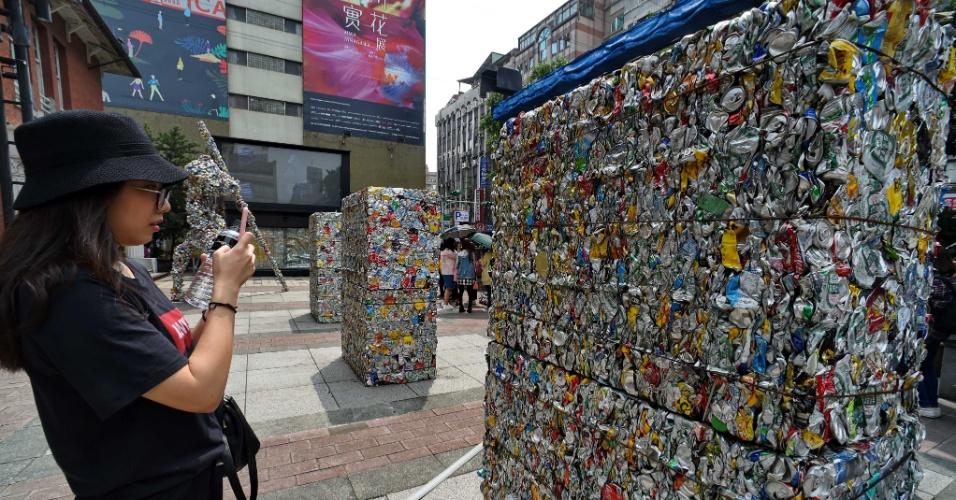 5.abr.2016 - Turista tira fotos de obra de arte feita com latas de alumínio amassadas em Taipei, Taiwan. Diversos trabalhos feitos de latas foram expostas nas ruas da cidade para chamar a atenção para a proteção do meio ambiente