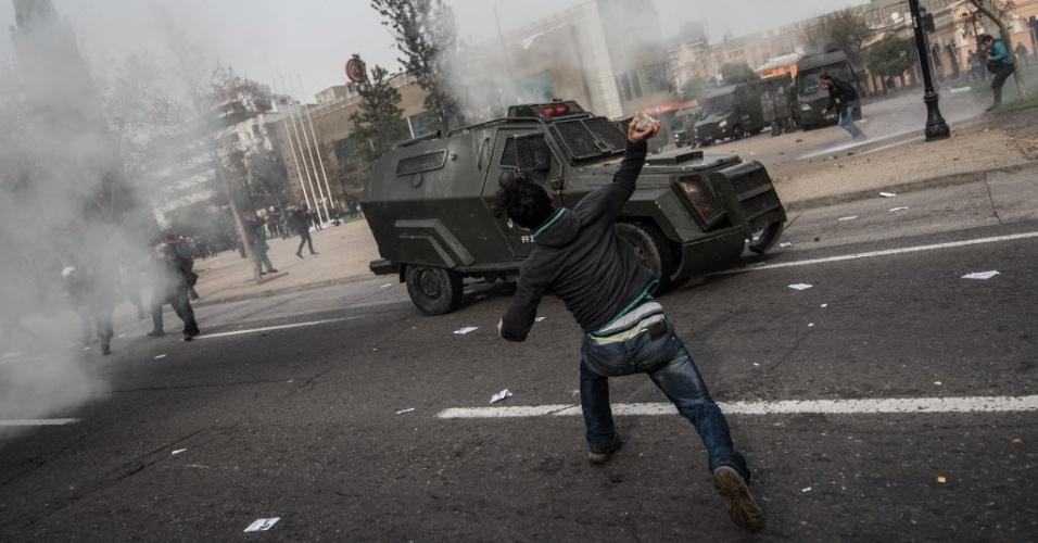 """23.jun.2016 - Um manifestante joga uma pedra contra um tanque policial durante protesto organizado por estudantes em Santiago, no Chile. O ato usou a frase: """"chegou a hora de uma educação pública, gratuita e de qualidade"""" para exigir melhores condições e se opor a uma reforma educacional promovida pelo governo"""