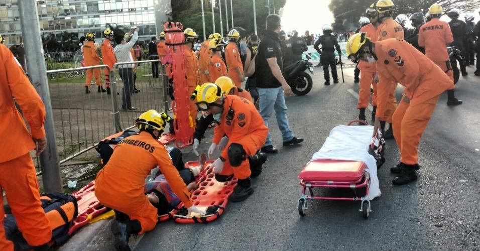 24.mai.2017 - Mulher é socorrida por bombeiros após ficar ferida durante protesto na Esplanada dos Ministérios, em Brasília