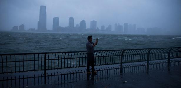 29.out.2012 - Homem tira foto em Battery Park City, em Manhattan, durante a aproximação do furacão Sandy em Nova York
