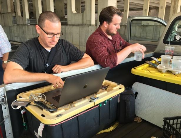 Fotógrafo Joshua McKerrow (à esq.) e jornalista Chase Cook trabalharam em estacionamento para conseguir fechar edição do jornal de Annapolis após ataque - AFP PHOTO / Ivan Couronne
