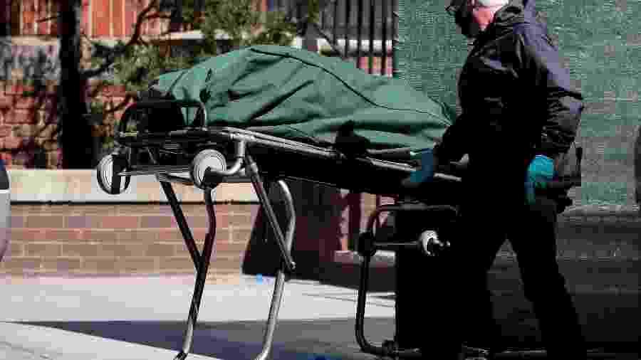 Trabalhador transporta corpo de pessoa morta em hospital no Brooklyn, em Nova York, em meio à pandemia de coronavírus - BRENDAN MCDERMID