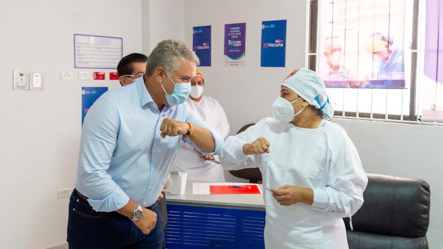 17.fev.2021- O presidente da Colômbia Ivan Duque cumprimenta a enfermeira chefe do Hospital Universitário de Sincelejo, Veronica Machado, no primeiro dia de vacinação contra a covid-19 no país - Reuters