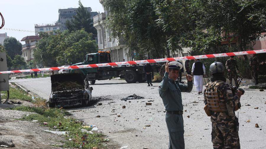 20.jul.2021 - Seguranças montam guarda perto de um veículo carbonizado de onde foram disparados foguetes que pousaram perto do palácio presidencial afegão em Cabul - AFP