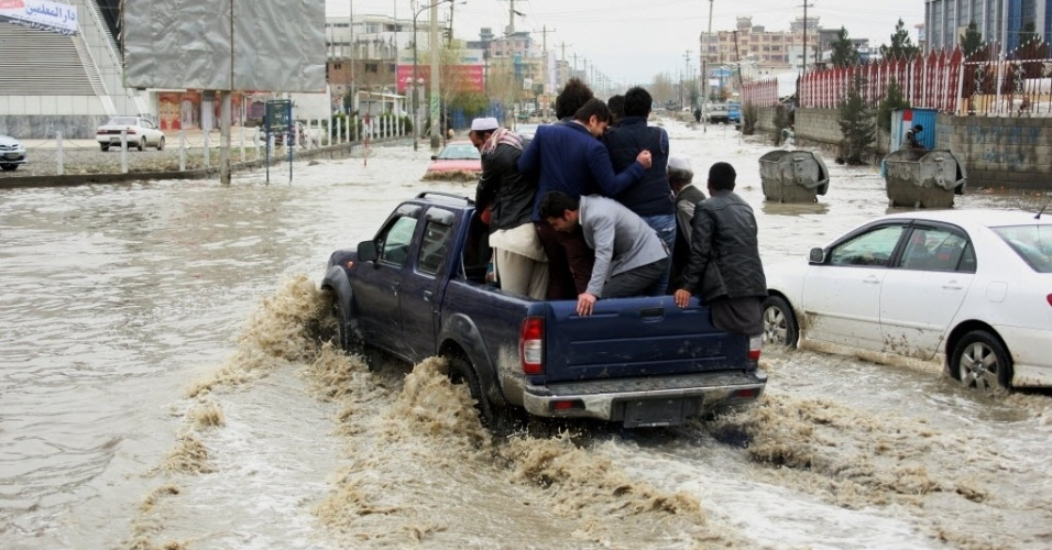 14.mar.2016 - Homens entram na caçamba de uma caminhonete para conseguir atravessar uma estrada alagada após forte chuva no centro de Cabul, Afeganistão