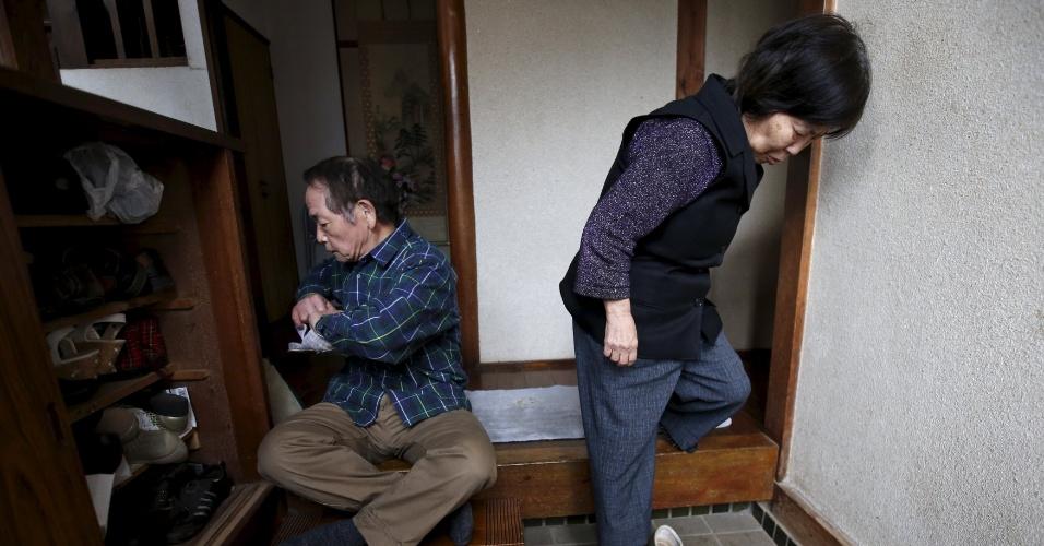 18.abr.2016 - Kanemasa Ito, 72, arruma os sapatos dentro do armário junto com a mulher, Kimiko, 68, que foi diagnosticada com demência há 11 anos, enquanto se preparam para fazer compras em Kawasaki, no sul de Tóquio (Japão). Encorajar pacientes com demência a falar sobre o tema faz parte dos esforços do governo para aliviar a imagem negativa desse que já afeta cerca de 5 milhões de cidadãos, número que deve aumentar para 7 milhões, até 2025 -- ou um em cada cinco japoneses com 65 anos ou mais
