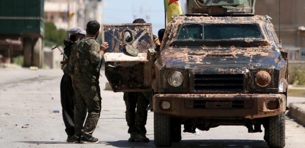 Combatentes curdos do YPG e seu veículo militar próximo à cidade de Qamishli, na Síria