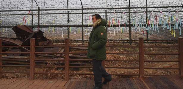 Homem passa por cerca próximo à zona desmilitarizada que divide as duas Coreias
