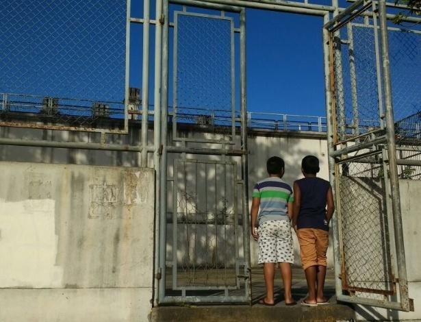 Garotos observam muro da cadeia a partir da quadra onde não podem mais jogar futebol - UOL