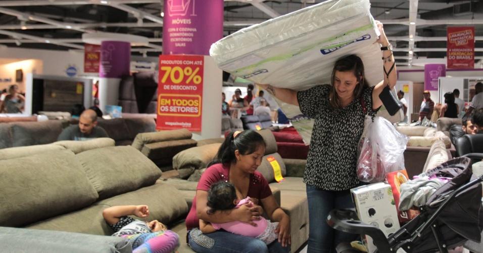 6.jan.2017 - Mulher carrega colchão de solteiro durante dia de liquidação, em loja na Marginal Tietê, na zona norte de São Paulo