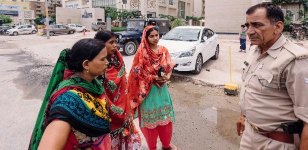 Mulheres de maridos que foram presos no tumulto no Mahagun Moderne falam com policial, em Noida, Índia