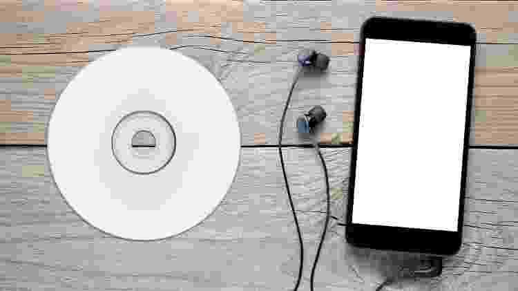 Smartphone com fone de ouvido e um CD; música - iStock - iStock