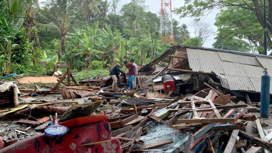 Moradores entre os destroços do tsunami perto de Anyer Beach na Indónesia - EPA