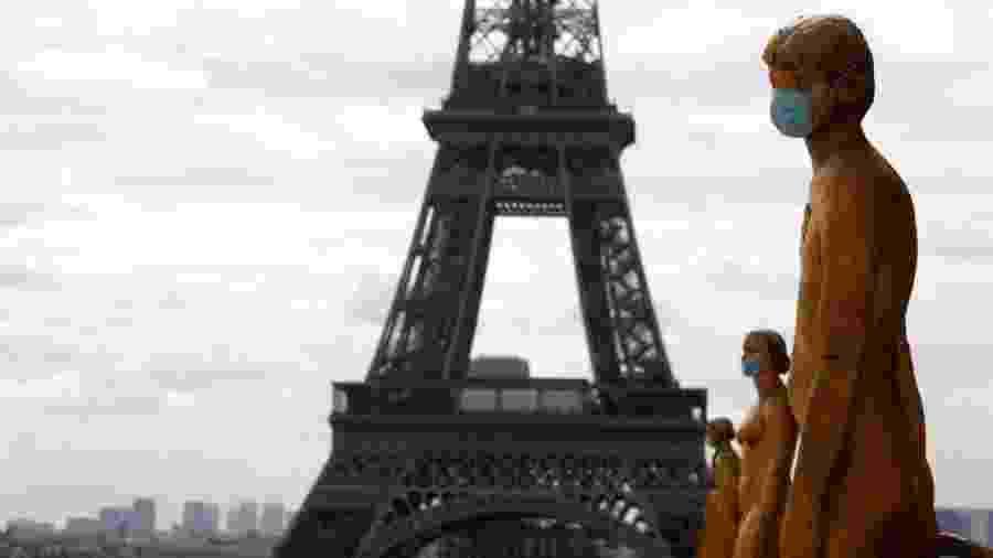 """4.mai.2020 - Estátuas usam máscara para se """"proteger"""" do novo coronavírus; ao fundo, a Torre Eiffel, em Paris, na França - Mehdi Taamallah/NurPhoto via Getty Images"""