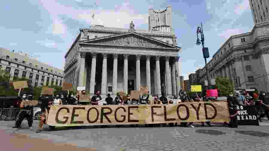 Manifestantes exibem cartazes contra o racismo em Nova York após a morte do segurança negro George Floyd em uma abordagem policial - Justin lane/Efe