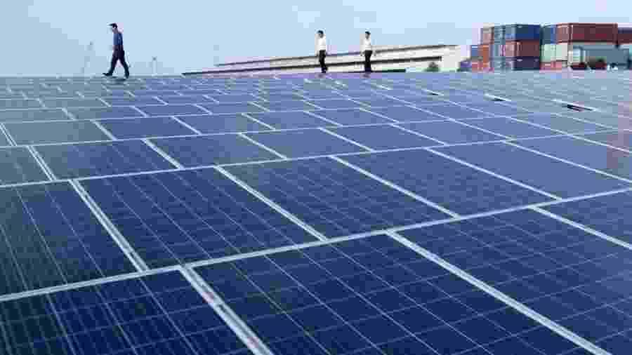 O CEO da Sun Electric, Matthew Peloso (esq.), caminha entre os painéis solares no telhado de uma fábrica em Cingapura - Reuters