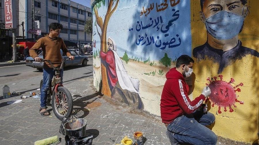 Artista palestino produz mural alertando sobre a covid em Rafah, no sul de Gaza - Mohammed Abed/AFP