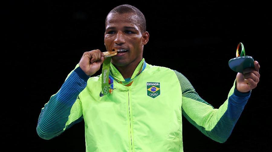 Boxeador brasileiro Robson Conceição morde a medalha de ouro da categoria leves - Peter Cziborra/Reuters