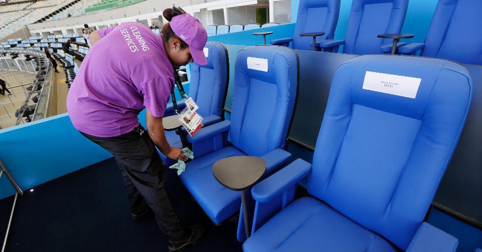 Funcionária limpa poltronas da tribuna presidencial, antes da Cerimônia de Abertura no Maracanã