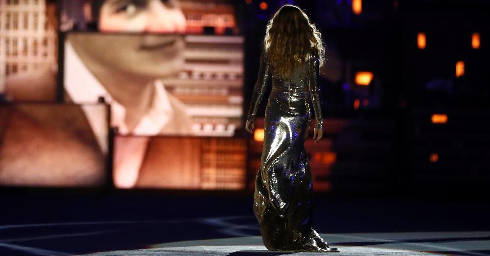 """Gisele Bündchen desfila ao som de """"Garota de Ipanema"""". Imagem do compositor Tom Jobim aparece ao fundo"""