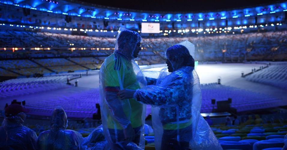 Casal se protege da chuva com capas antes da cerimônia de encerramento