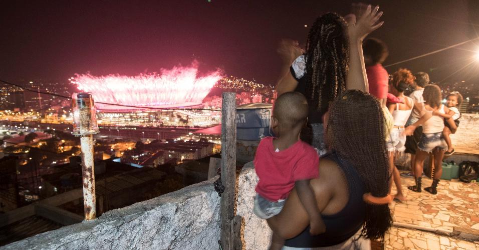 Moradores de comunidade do Rio acompanham os fogos de artifício da cerimônia de abertura