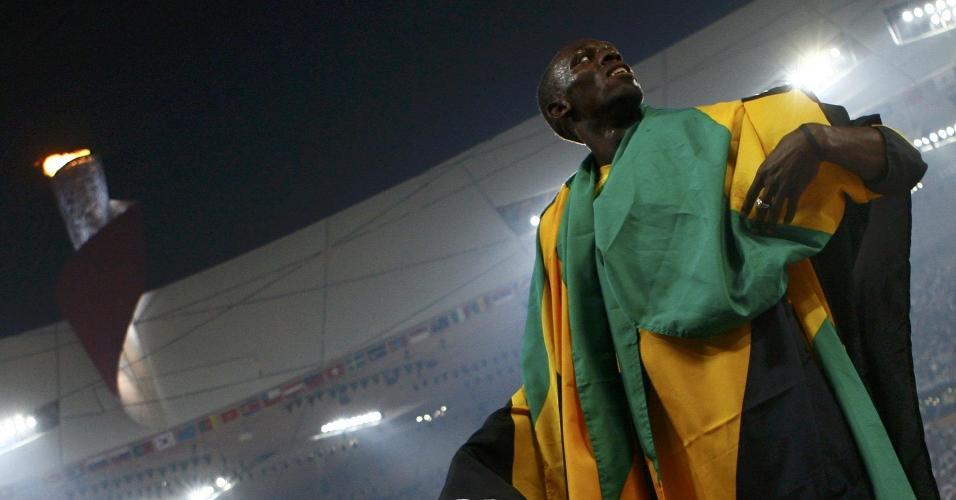 Usain Bolt, com a sapatilha dourada na mão e coberto com bandeiras da Jamaica, comemorando o título dos 200 m rasos de Pequim-2008