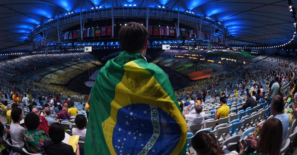 Enrolado em bandeira do Brasil, torcedor aguarda o início da cerimônia