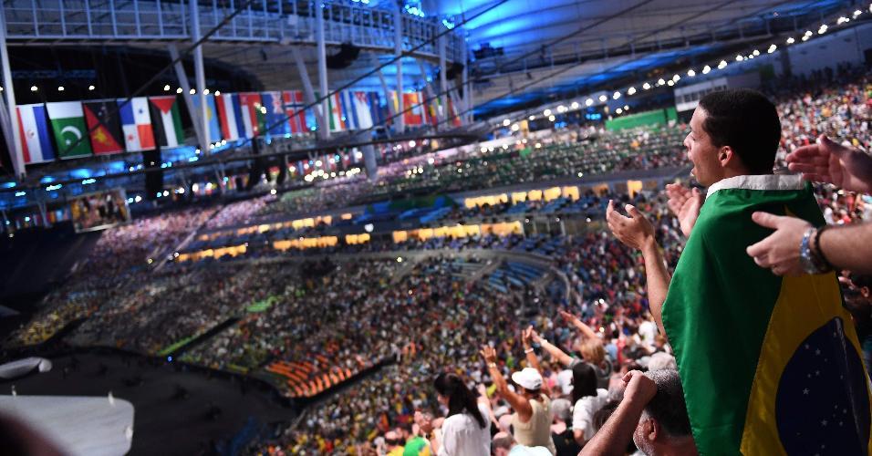 Espectador aplaude o início da cerimônia de abertura dos Jogos