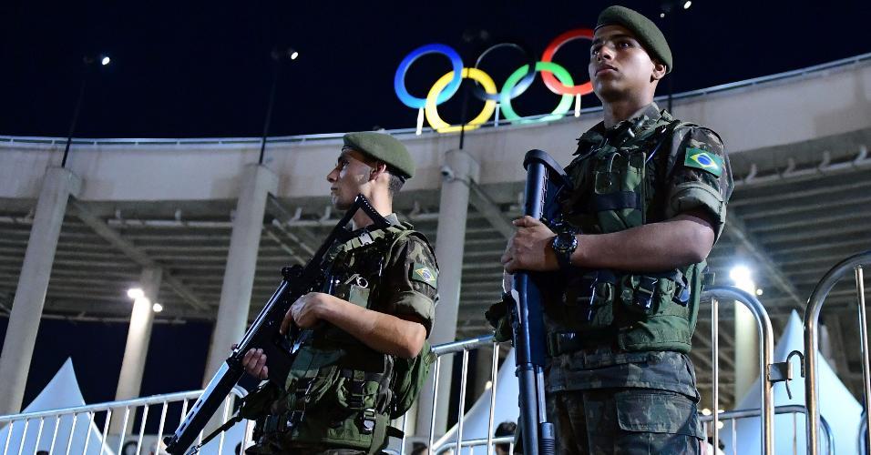 Membros da Exército observam a chegada do público à cerimônia de abertura dos Jogos