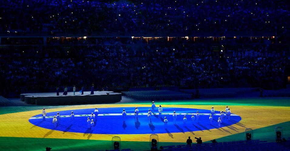 Projeção com a bandeira do Brasil aparece no gramado do Maracanã durante a cerimônia de encerramento