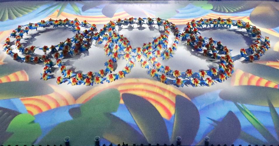 Dançarinos reproduzem os arcos olímpicos no gramado do Maracanã, durante a cerimônia de encerramento dos Jogos