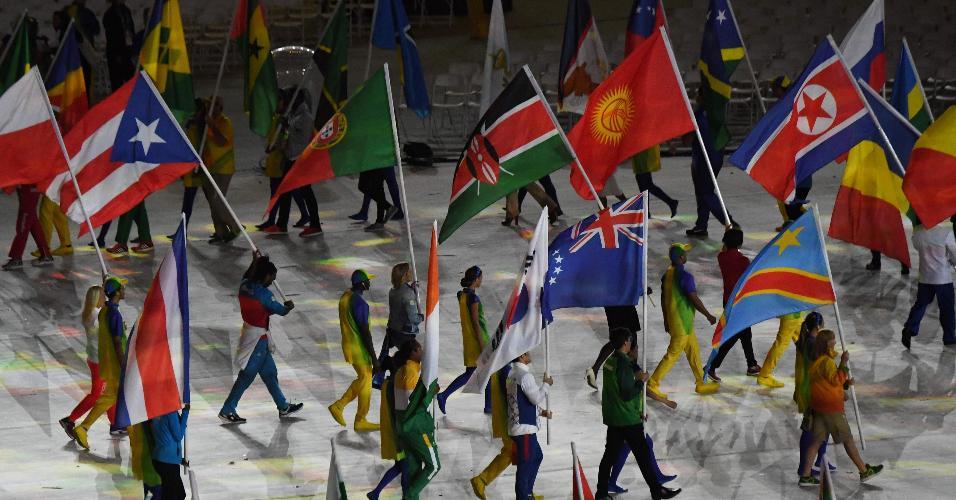 Atletas entram no gramado do Maracanã carregando as bandeiras de seus países na cerimônia de encerramento